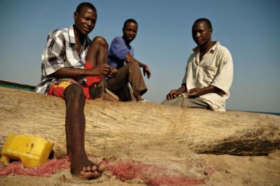 Trois pêcheurs sur une pirogue sur la plage de Cape Maclear, Malawi