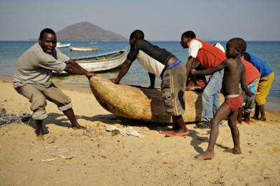 Hommes qui tirent une pirogue sur la plage à Cape Maclear, Malawi
