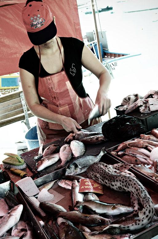 Femme qui découpe des poissons au marché de Marsaxlokk, Malte