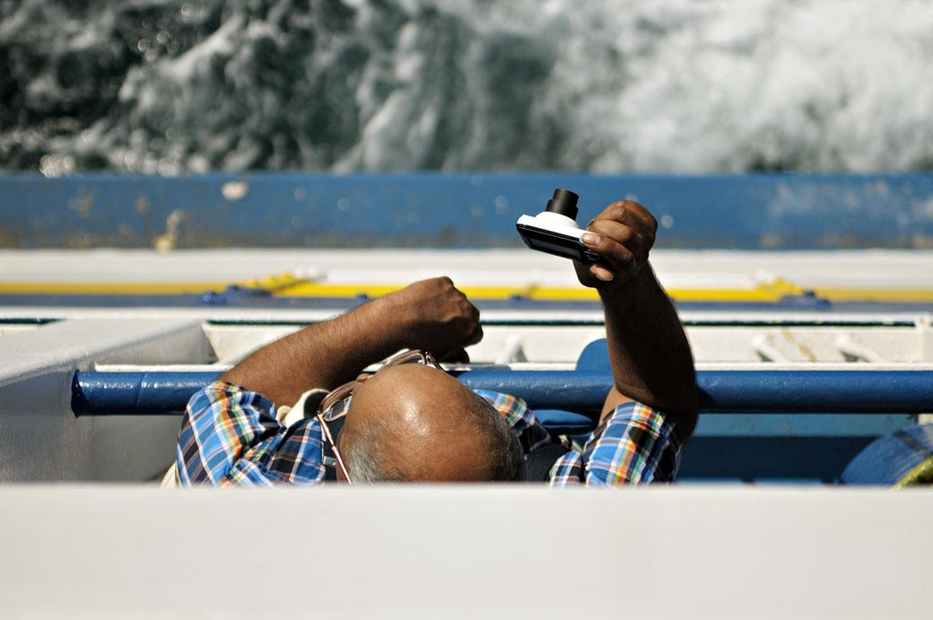 Homme qui prend une photo sur le ferry pour Gozo