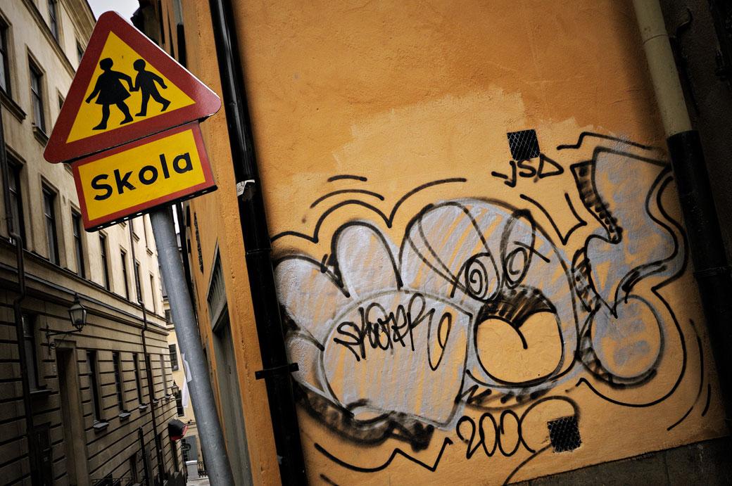 Panneau Skola et graffiti à Gamla Stan, Stockholm