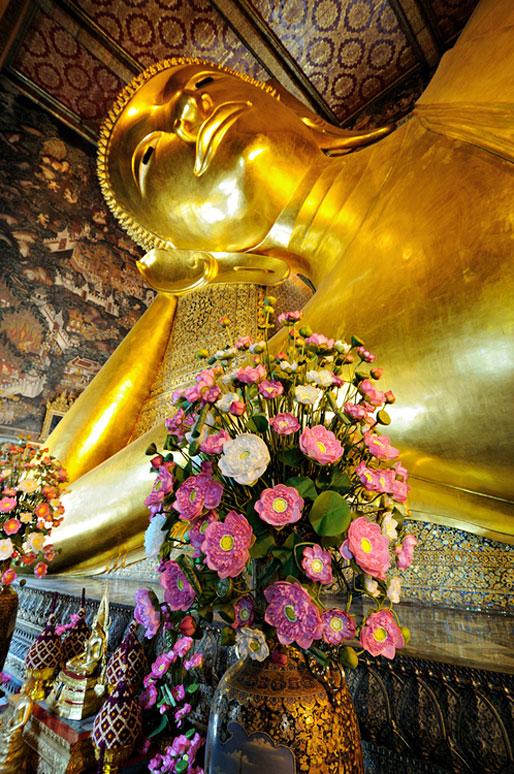 Fleurs et bouddha couché du Wat Pho à Bangkok, Thaïlande