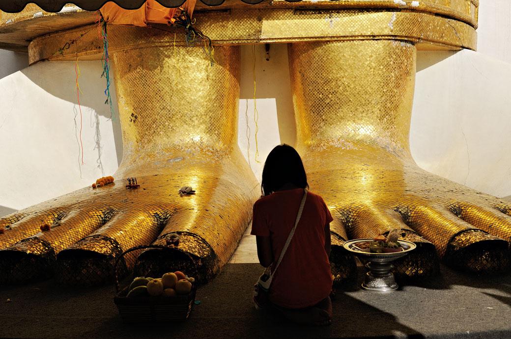 Femme qui médite au pied du Bouddha de Wat Intharawihan à Bangkok