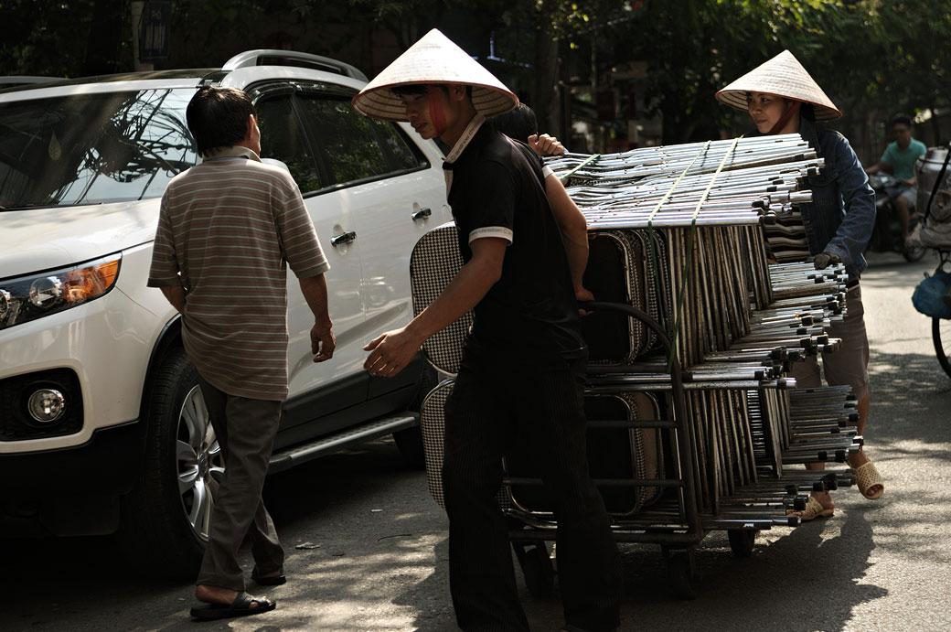 Transporteurs de chaises dans une rue de Hanoi, Vietnam
