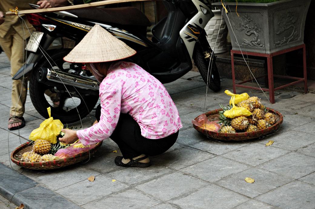 Vendeuse de fruits dans une rue de Hanoi, Vietnam