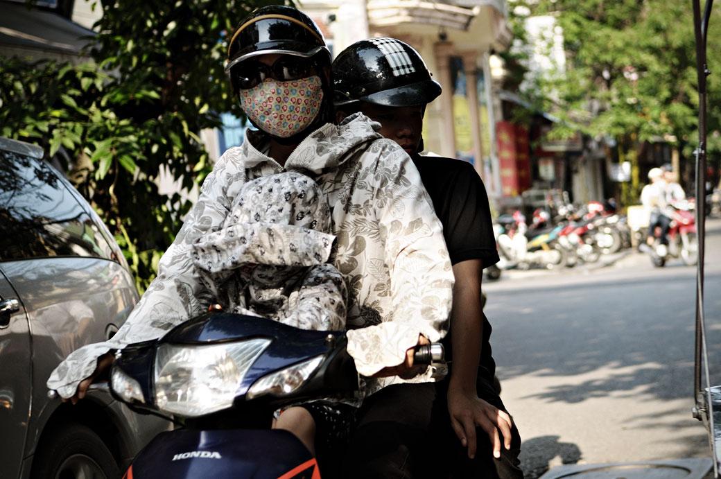 Femme avec un masque sur un scooter à Hanoi, Vietnam