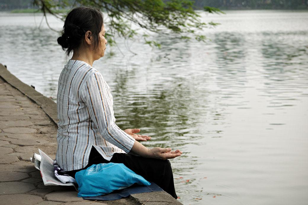 Femme qui médite au bord du lac Hoan Kiem à Hanoi, Vietnam