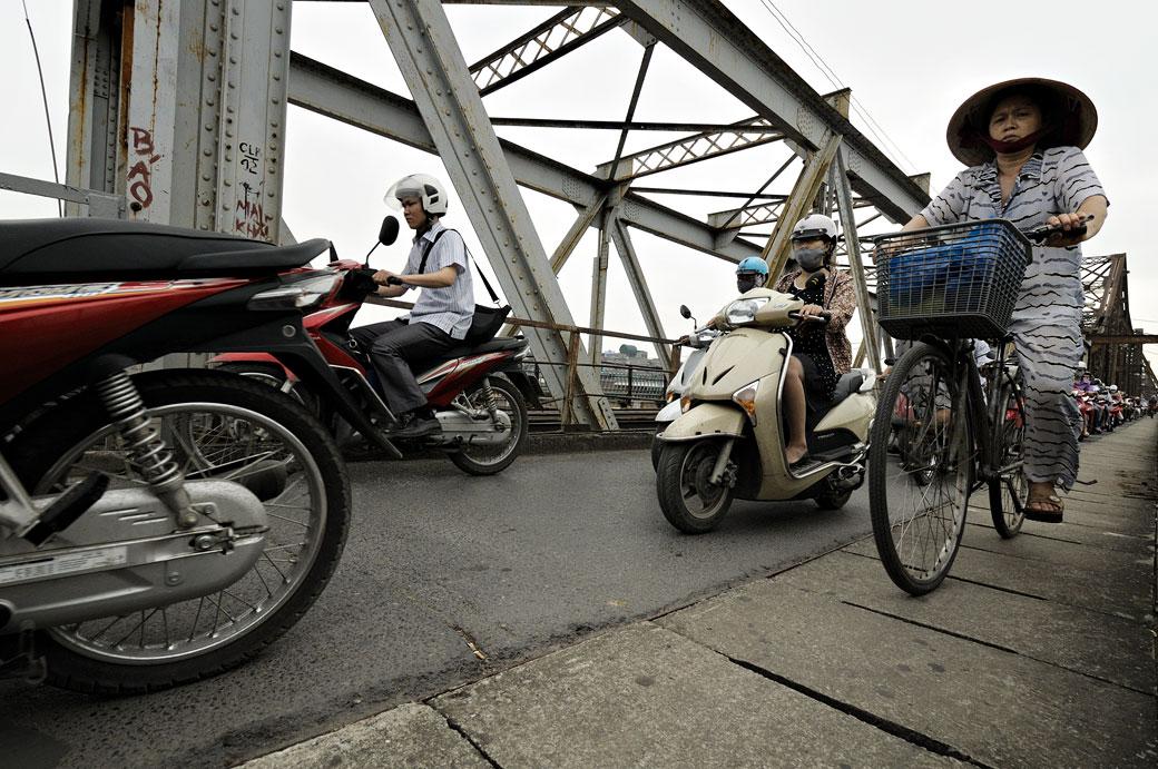 Femme à vélo sur le pont Long Biên à Hanoi, Vietnam