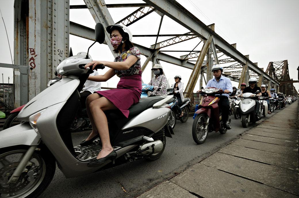 Femme à scooter sur le pont Long Biên à Hanoi, Vietnam