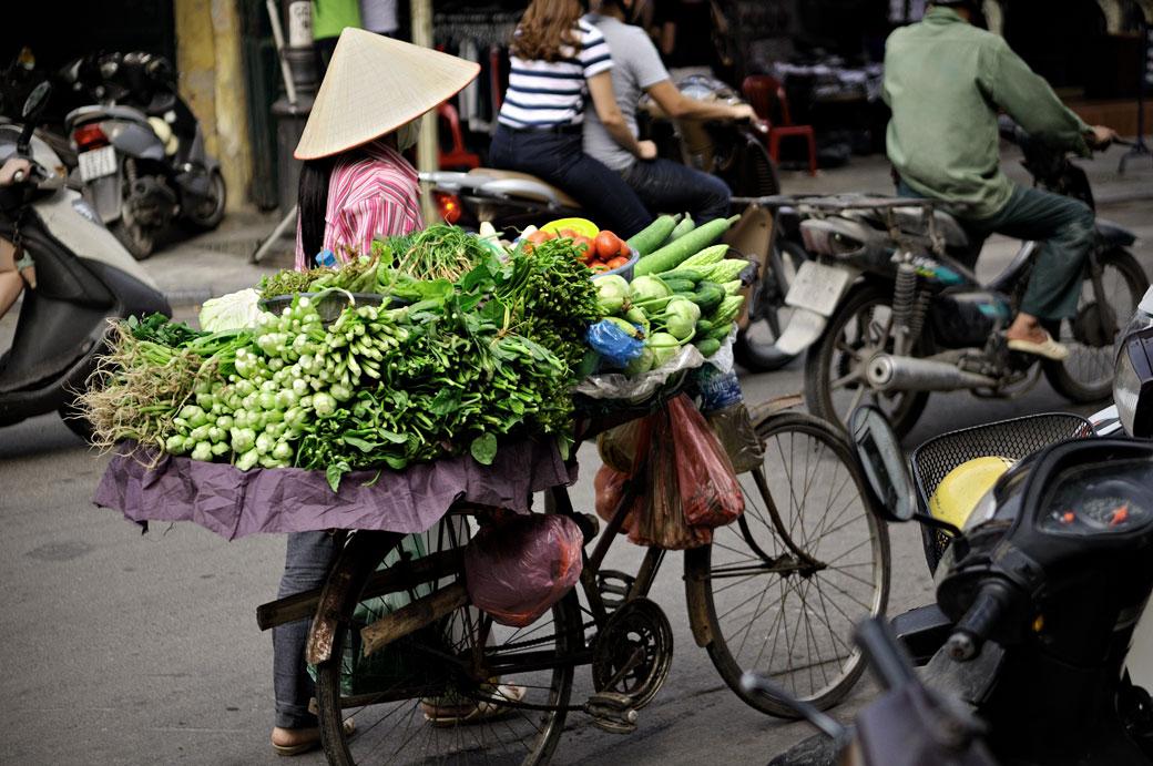Vendeuse de légumes à vélo à Hanoi, Vietnam