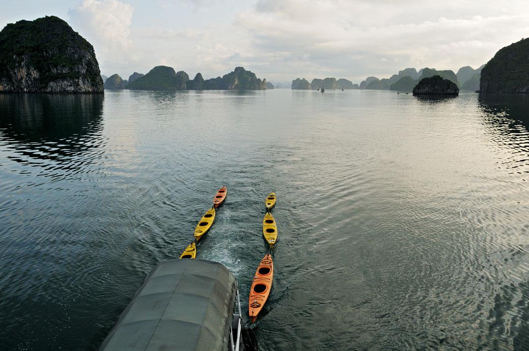 Bateau tirant des kayaks dans la baie d'Halong, Vietnam