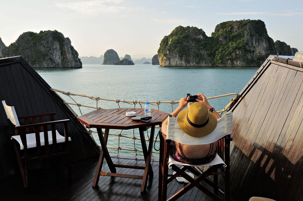 Femme qui se relax sur le pont d'un bateau dans la baie d'Halong
