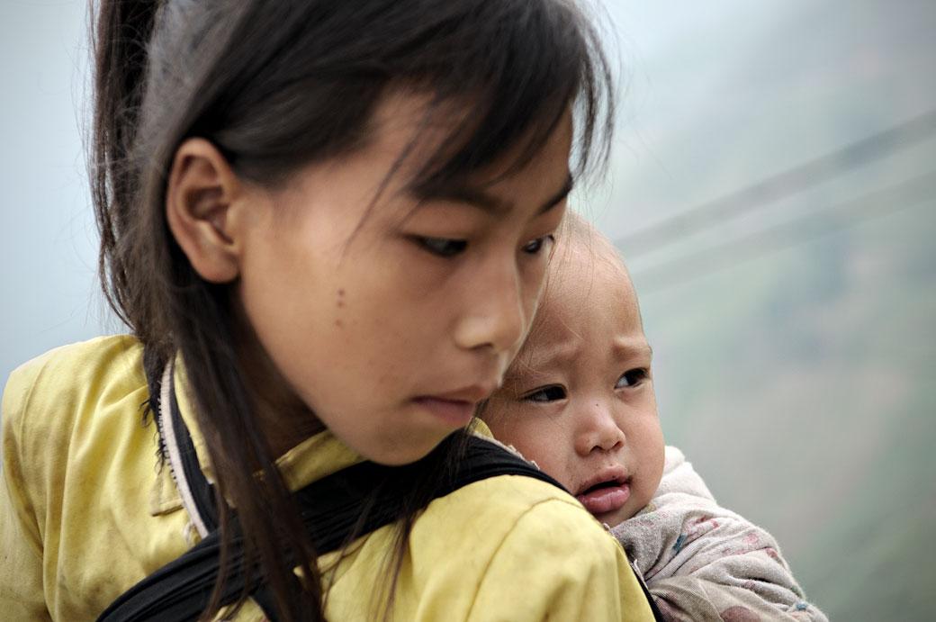 Bébé sur le dos de sa soeur, Vietnam