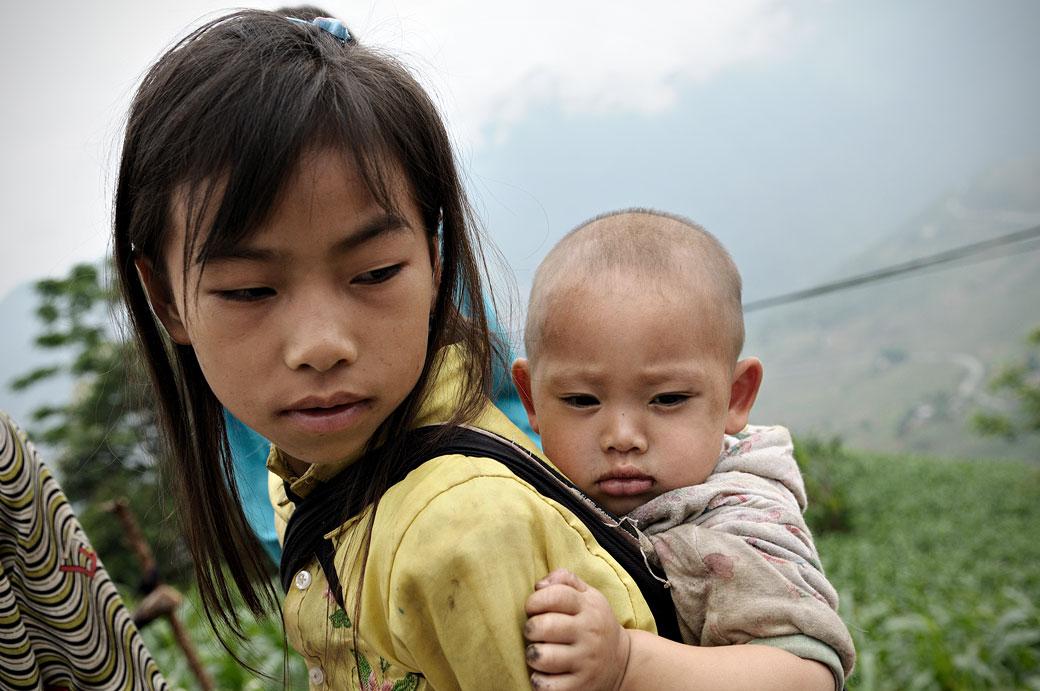 Jeune fille avec son frère sur le dos, Vietnam
