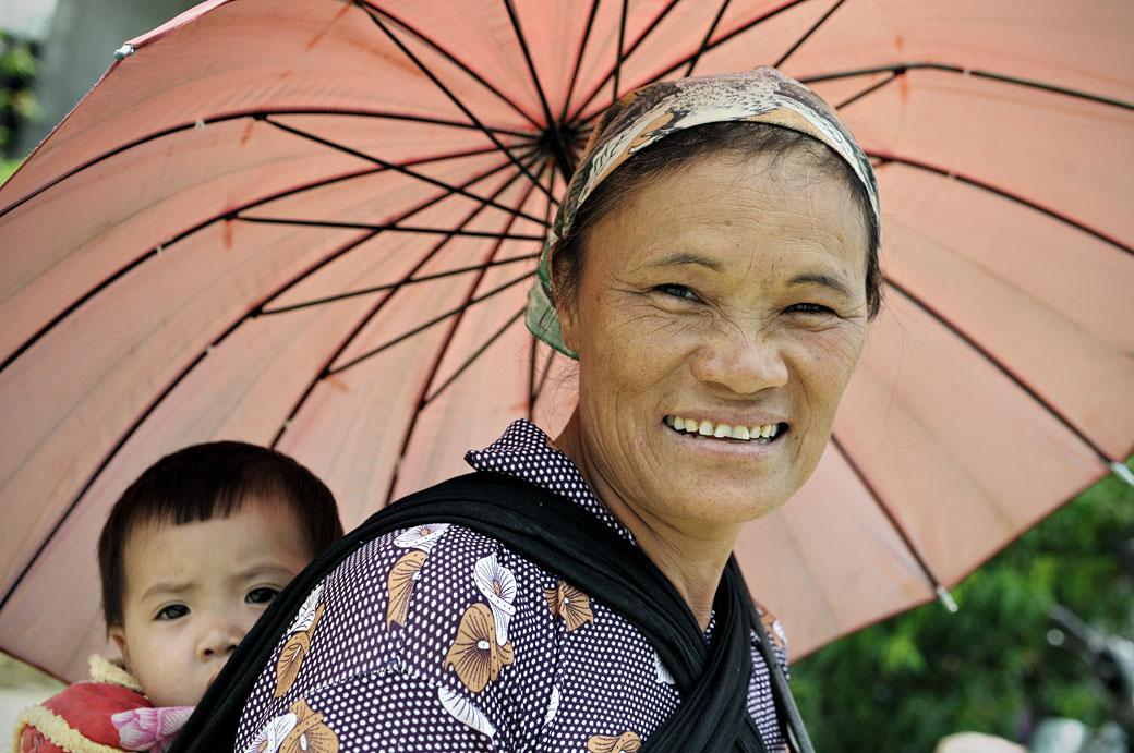 Femme et bébé sous une ombrelle à Quyet Tien, Vietnam